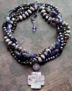 """""""byzantium - a dark shade of purple"""" which this gorgeous piece has ... not to mention violet, lavender, eggplant, grape, and tyrian (another new purple name!) ... among these four intermingling strands of purple you'll find a full strand of faceted flower sugilite rondelles, grape amethyst nuggets, faceted crystals, and oodles of freshwater pearls -- dangling just below is a fantastic flower sugilite Celetic cross pendant ..Mia Bella....Again look on line for these stones! Ebay!!"""