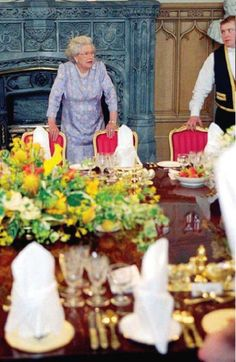 Queen Elisabeth II arranging a dinner´s detail.