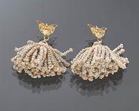 Gouden akerhaakjes  Op de afbeelding staan een paar gouden akerhaakjes met daaraan geknoopte akertjes. De tulpvormige akerhaakjes zijn van ongewaarborgd goud. Akertjes worden op Marken aan de punten van de schouderdoekjes gedragen.