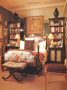 mirrored wall in this luxe small bedroom with chintz headboard, x-stool, art and books ~ elegant!