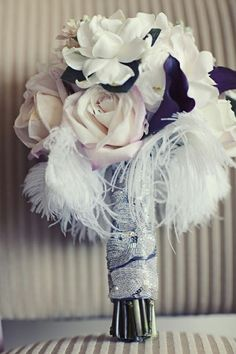 Feathers and flowers make a lovely wedding bouquet  www.finditforweddings.com