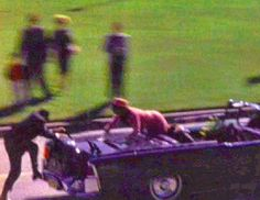 Clint Hill is the first to reach the Presidential limousine after the President's assassination, on Friday, 11/22/63.