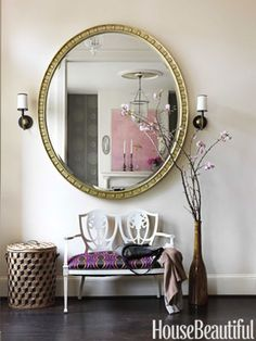 The Sophia mirror by Thomas O'Brien for Hickory Chair opens up the foyer and looks even bigger paired with an undersize vintage bench, updated in white lacquer and covered in Osborne & Little's Curva.