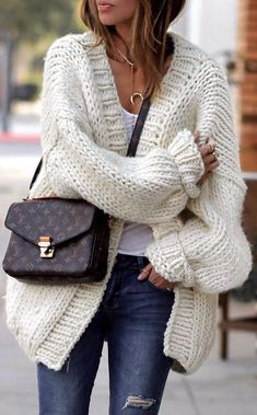 Cozy oversized white cardigan over white tee and blue jeans with chic handbag.