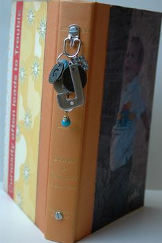 How to turn an old book cover into a mini ablum - use Tim Holtz binder rings