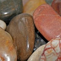 No matter how rough and chipped your collected rocks start out, they'll inevitably become smooth if they remain under moving water for several years. They look store-bought when smoothed and can be painted or varnished. Small-sized river rocks can be polished in a rock tumbler, while larger rocks must be varnished or shellacked to make them shiny.
