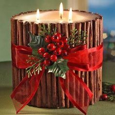 3-wick candle wrapped in cinnamon sticks which are tied together with a red ribbon and some greenery with red berries worked into the bow.
