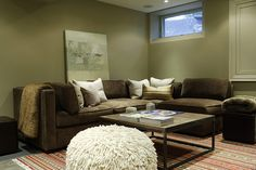 Living room with olive walls, colorful lineal rug and brown sectional couch.