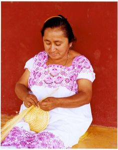 A worker at the Hacienda Santa Rosa makes a henequen basket. She wears a version of the Mayan huipil, the embroidered blouse or dress.