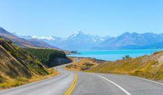 A road winds alongside a glistening lake in New Zealand