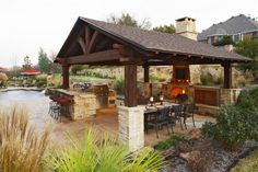 This enormous gazebo features stone supports, a large stone fireplace, a grill and outdoor cooking area, and even a large dining table.