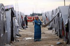 A Kurdish refugee woman from the Syrian town of Kobani opens her tent in a camp in the southeastern town of Suruc, Sanliurfa province October 23, 2014. REUTERS/Kai Pfaffenbach
