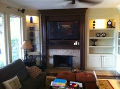 Custom Entertainment Wall. Tan cabinets with a dark stained mantel
