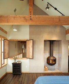 "loft bedroom has ""window"" to below and funky fireplace"