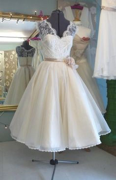 This short wedding dress is vintage and has the classic lace look for the bodice and sleeves. The blush colored ribbon that wraps around the waist is a beautiful adornment and really brings out the figure.