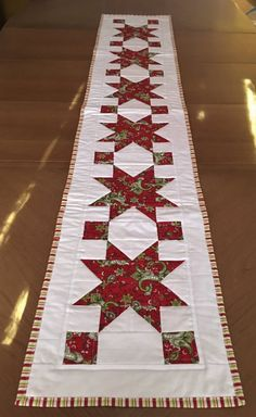 This quilted table runner would be a striking start for any Winter table. It can grace your Christmas dining table or be part of your coffee table decor for Winter. Six stars in a red and green paisley and flower motif run down the center of this holiday table runner. They are accented