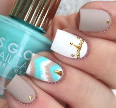 Turquoise, beige avid white nails with jewel detail.