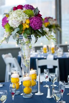 Lemons in water with candles are creative for a summer wedding. If our centerpieces do not contain a yellow flower, it might be a creative way to introduce color on the tables.