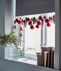 Dans l'embrasure d'une fenêtre, le bas d'un store blanc est orné de décorations IKEA DECO