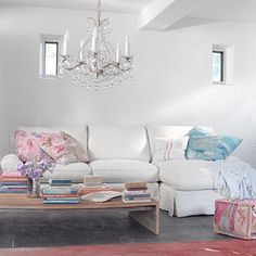 Beach shabby cottage decor with white slipcover sofa, chandelier, lots of books and colorful soft pillows.