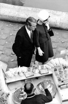"""The actor Cary Grant photographed with the actress Audrey Hepburn by Giancarlo Botti in Paris (France), during the filming of their new movie """"Charade"""", in December 1962. Audrey was wearing: • Suit: Givenchy (of red wool, short coat with buttons..."""