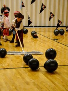 Swab the deck game. Children push balloons around with a mop or broom.