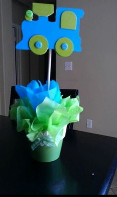 Center Piece I made for my son's baby shower. Train theme. Suppper easy bought the trains at the dollar store, painted them from Cheap Wal-mart paint and purchased sticks to glue gun them onto Styrofoam.  Pots also from dollar store and covered all the mess inside with tissue paper. MRS. HILL