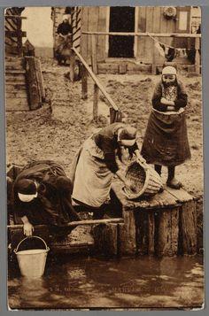 Drie vrouwen in werkdracht bij de boenstoep, ca. 1910. Rechts haalt een vrouw een emmer water uit de sloot. Het meisje rechts is Niesie Schouten. Op de achtergrond wasgoed en huisjes. 1905-1915 #NoordHolland #Marken