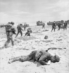 A dead US soldier in the sand as other troops and tanks move off the beach, Utah/6 June 1944.