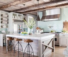 Spacious old-world kitchens call for high-impact surfaces, materials, and fittings. Note this room's extra-thick marble countertops, bronze pendant lights, and steely range hood. The island takes center stage against a mint backsplash thanks to cross-hatch details and a facade crafted from horizontally-set aged boards./