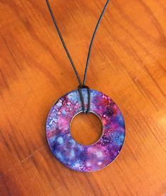 I like that the used cord instead of chain.  We'd avoid having to close the jump rings and it may be cheaper - Alcohol Ink Washer Necklace #galaxy #upcycle