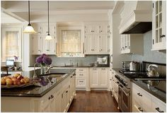 white cabinets, black granite, blue backsplash with wood floors - love this but brown / cream counter