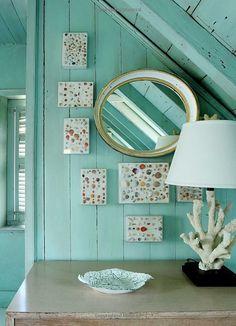Aqua walls, coral lamp, and seashell art on the walls