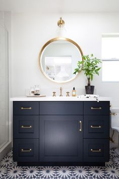 Guest house bathroom with a round vanity mirror, designed by Kristen Marie Interiors, via @sarahsarna.
