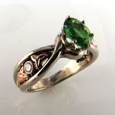 Green Tsavorite Gold Celtic Ring. Custom 14K White and Rose Gold Celtic ring. Set with a Green Tsavorie and two small diamonds. Prices of custom rings vary by width of the ring, complexity of style an