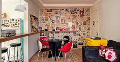 Papéis de parede ajudam a trazer mais personalidade para a casa. Nesse caso, parede com jornal e muita cor nos móveis e acessórios.