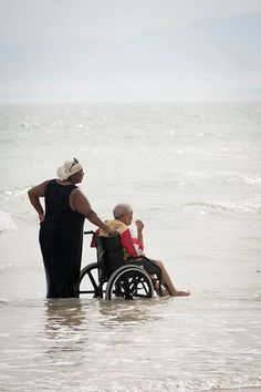 Daughter helping her mother into the waves in Cape Town, South Africa