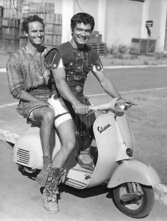 This is classic! Ben Hur, riding bitch on a Vespa. 1959. Love it!