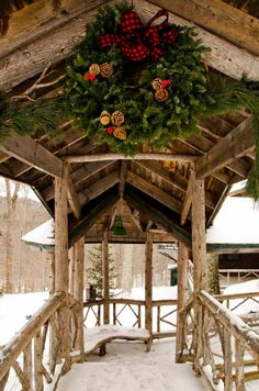Christmas wreath on rustic styled walkway covered with snow