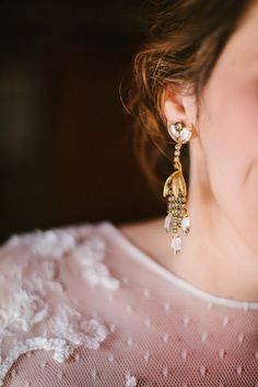 Don't be afraid to go big with your earrings, especially when your necklace keeps you from adding on a big necklace. Photo by Cluney Photo via Style Me Pretty
