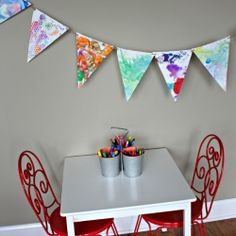 Here is a simple and fun way to display your child's masterpieces - transform them into a bunting for their bedroom or playroom!