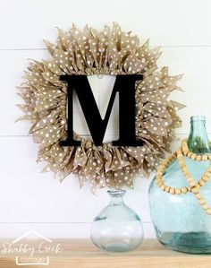Add some farmhouse wall decor to your front door! Make your own beautiful monogrammed burlap wreath that's perfect for any season.