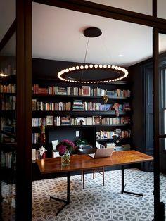 escritório com luminária circular pendente e piso estampado