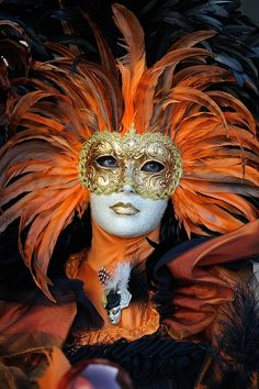Venice Carnevale...ooh, orange feathers and a gold mask on mask for a lady.