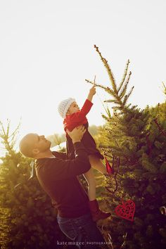 daddy holding her up to put ornament/star on tree