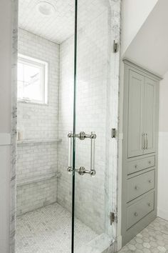 A seamless glass door fitted with a nickel and lucite handle opens to a stunning marble clad walk-in shower boasting stacked marble ledges mounted beneath a window framed by marble subway tiles.