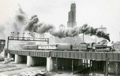Old steam train leaving Chicago - Sears Tower in the background