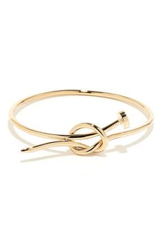 "You can travel around the world, from London to the bay, but nothing can quite touch the unique look of the Hammer Time Gold Nail Bracelet! This shiny gold bracelet has the look of a knotted nail, perfecting for pairing with your favorite watch or bangles! Bracelet has a 2.5"" diameter. Man made materials. Imported."