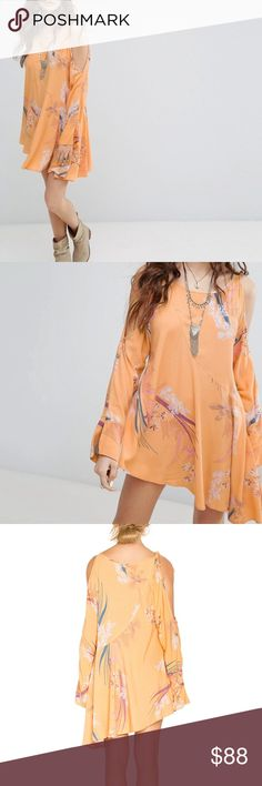 Free People Clear Skies Printed Tunic in Orange Color listed as orange but seems like a golden yellow to me. Tunic. Scoop neckline. Pullover style. Can be worn as a mini dress.  Flowy and flattering, this Free People tunic is made of the season's most cheerful shade with a serene floral print scattered throughout. Exposed shoulders and an asymmetric hem lend a laid-back approach to this darling day dress. Unlined with open shoulders / cold shoulder detail. Tie detail at right shoulder…