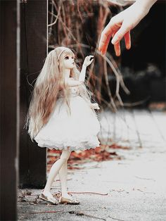 Lovely doll reaching for her friend. What a great photo idea.